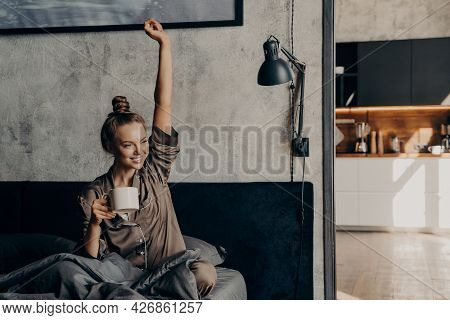 Happy Life. Attractive Young Happy Female Having Morning Coffee In Bed After Waking Up, Dressed In S