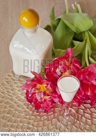 Bottle Of A Coconut Liqueur With A Small Glass With Some Beautiful Flowers In The Background
