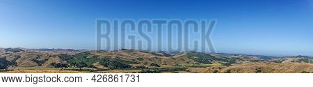 Cambria, Ca, Usa - June 8, 2021: Panorama Landscape Of Ocean And Back Country With Dry Ranch Land An