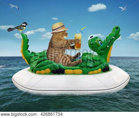 A Beige Cat In A Straw Hat With A Glass Of Juice Is Floating On An Inflatable Crocodile In The Sea A
