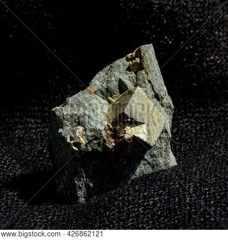 Shiny Cubic Crystal System Pyrite Fools Gold Mineral From Ural, Russia. A Backlight Photo Of A Stone