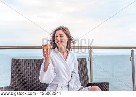 Young Woman In White Bathrobe Is Eating Pink Donut With Marshmallows While Sitting On Open Terrace B