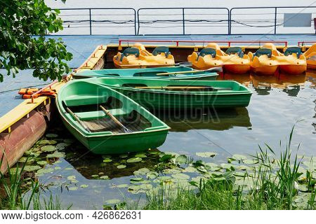 Boat Station On The Lake. Boats And Pedal Boats On The Water. Water Lilies Grow In The Water.
