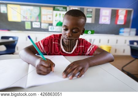 African american boy studying while sitting on his desk in the class at elementary school. school and education concept