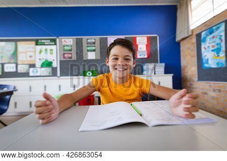 Portrait of caucasian boy smiling while sitting on his desk in the class at elementary school. school and education concept