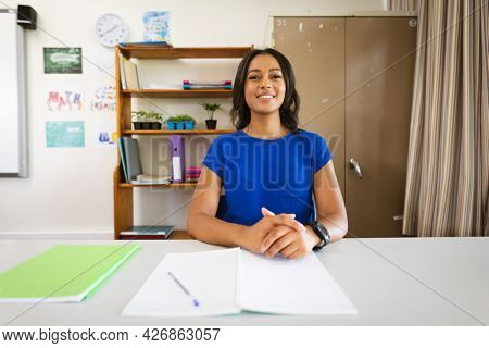 Portrait of african american female teacher smiling while sitting on her desk at elementary school. school and education concept