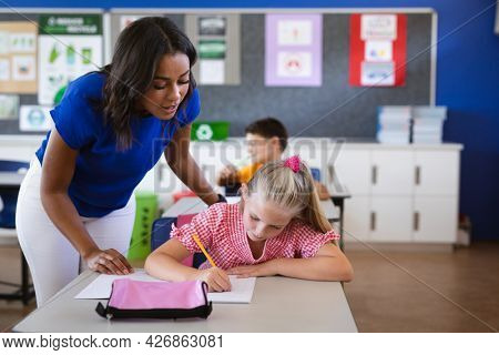 African american female teacher teaching caucasian girl in the class at elementary school. school and education concept