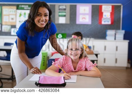 African american female teacher and caucasian girl smiling in the class at elementary school. school and education concept