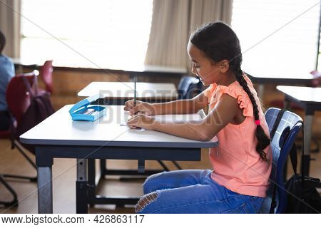 African american girl studying while sitting on her desk in the class at elementary school. school and education concept