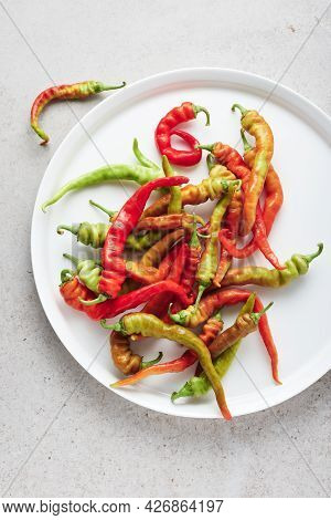 Fresh Red And Green Peppers In A White Dish.