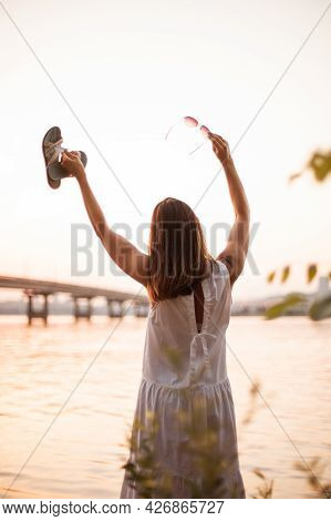 A Caucasian Woman Stands With Her Back With Her Hands Raised And Thanks The Sun, Meditates And Relax