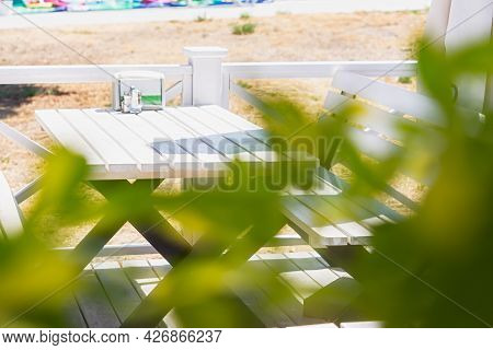 An Outdoor Cafe With White Wooden Tables And Seats. The Concept Of A Summer Holiday, Empty Bars And