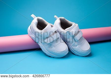 The Composition Is A Balance Of Two White Childrens Sneakers With Velcro Fasteners For Easy Footwear
