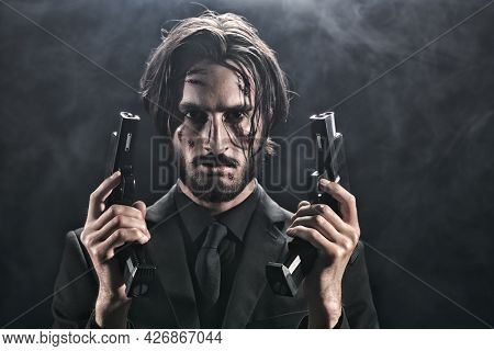 Handsome wounded action hero in a black suit with guns in his hands on a dark foggy background. Copy space.