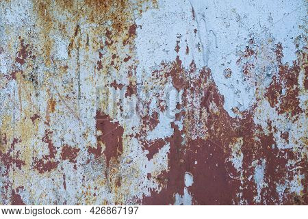 The Surface Of A Metal Wall With Several Crumbling Paint Layers And Traces Of Rust. It Looks Like A