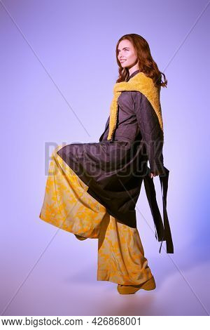 Fashion model girl poses in stylish clothes from the spring-summer collection. Haute couture clothing. Full length studio portrait on on a light purple background.