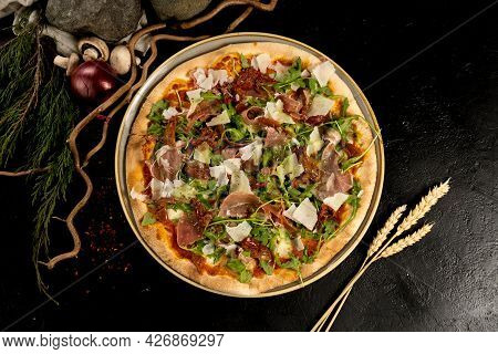 Pizza With Parma Ham, Parmesan Cheese, Dried Tomatoes And Arugula