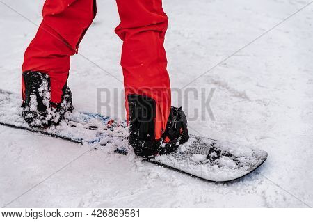 Legs Of Snowboarder Standing On Ski Slope Close-up. Winter Sports, Outdoor Activities Concept