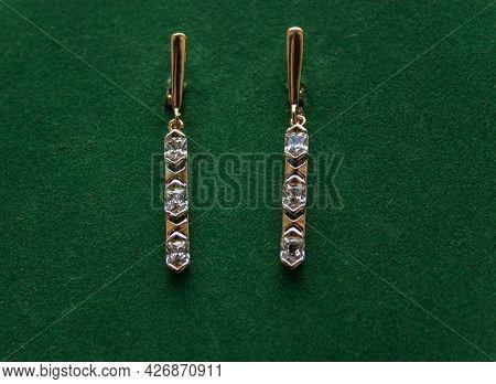 Jewellry Earrings With Gemsr On Green Leafs Background