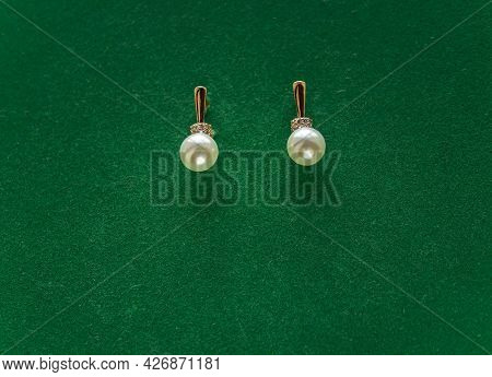 Set Of A Ring And Dangle Earrings Made Of Epoxy Resin With Golden Foil Inside Isolated Over Green Ba