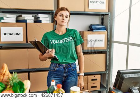 Young brunette woman wearing volunteer t shirt at donations stand looking sleepy and tired, exhausted for fatigue and hangover, lazy eyes in the morning.