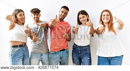 Group of young friends standing together over isolated background approving doing positive gesture with hand, thumbs up smiling and happy for success. winner gesture.