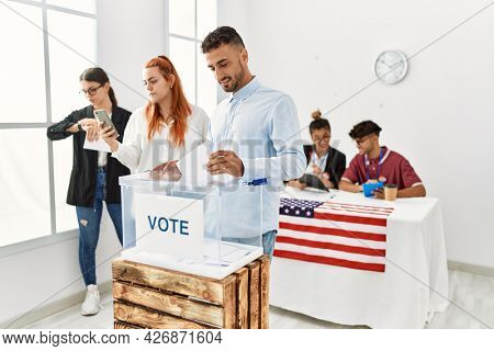 Young american voter man smiling happy putting ballot in voting box at vote center.