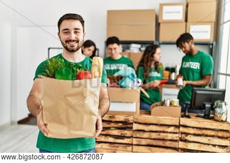 Group of young volunteers working at charity center. Man smiling happy and holding paper bag with food to donate.