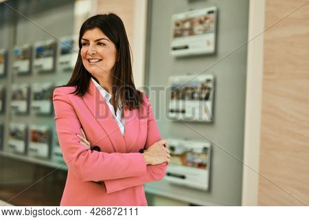 Middle age business woman working as real estate agent. Sales woman smiling happy at the office