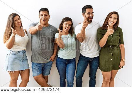 Group of young hispanic friends standing together over isolated background pointing fingers to camera with happy and funny face. good energy and vibes.
