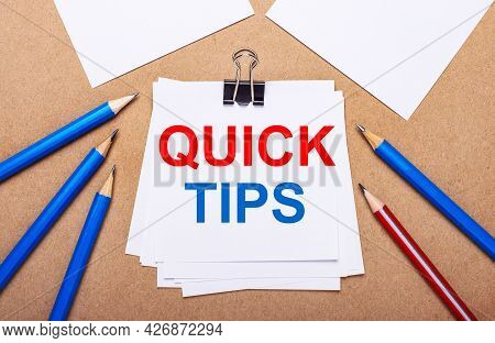 On A Light Brown Background, Blue And Red Pencils And White Paper With The Text Quick Tips