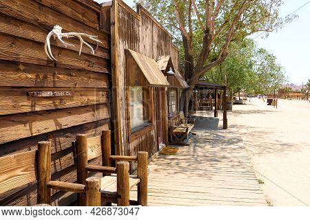 July 14, 2021 In Pioneertown, Ca:  Chairs Besides A Rustic Wooden Building With Hanging Antlers Take