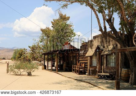 July 14, 2021 In Pioneertown, Ca:  Wooden Boardwalk Besides Historical Wooden Buildings And Cottonwo