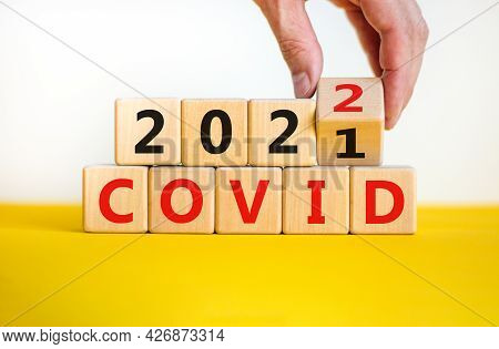 Covid-19 Pandemic In 2022 Symbol. Doctor Turns A Wooden Cube And Changes Words 'covid 2021' To 'covi