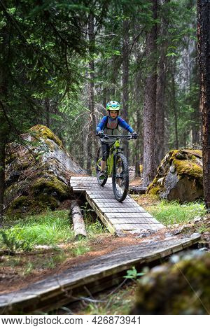 Banff Alberta Canada. July 7 2021: A Young Boy Rides His Mountain Bike Down A Wooden Ramp On The Top