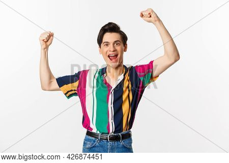 Image Of Happy Young Man Triumphing Of Winning, Celebrating Victory, Raising Hands Up In Rejoice And