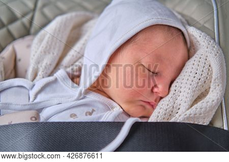 A Newborn Baby In A Car Seat Fastened With A Seat Belt
