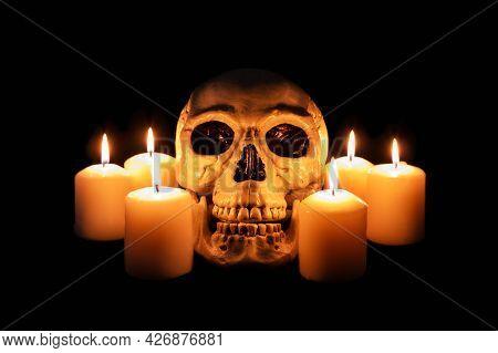 Human Skull Among Burning Candles In The Dark, Scary Still Life, Altar.