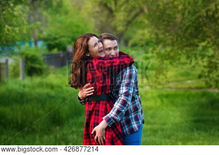 Loving Couple Hugging While Walking Relaxing In Summer Park Together. Girlfriend And Boyfriend Havin