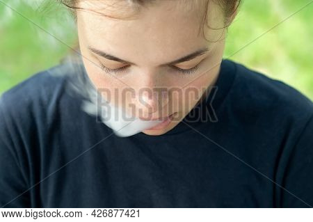 Vape Smokes. A Girl With Brown Hair Lets Off Steam From Her Mouth In Close-up. Portrait Of A Smoking