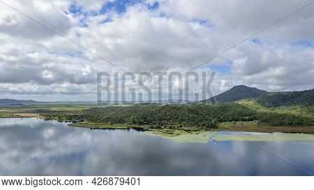 The Mirror Smooth Surface Of A Dam With Clouds Reflected In The Water. Kinchant Dam, Queensland, Aus