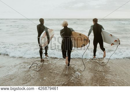 Surfers running towards the sea