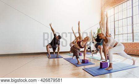 Sportive people doing Parivrtta trikonasana