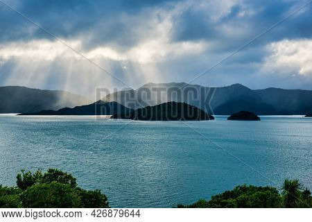 Sun Rays Breaking Through The Clouds  In Misty Rain Above The Islands In Waikawa Bay Picton