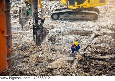 Construction Workers Sitting Among The Rubble Of Demolished Buildings With Working Machines.