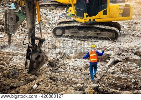 Construction Workers Standing Among The Rubble Of Demolished Buildings With Working Machines.