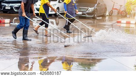 Selective Focus To Worker Using Wiper Or Squeegee To Clean Floor Surface. Staff Cleaning Floor With