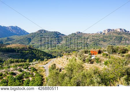 Costa Blanca Mountains View From Road With Red Building Among Trees In Area Around Tarbena, Spain
