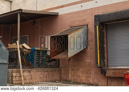 Shopping Carts Abandoned At A Unloading Dock Bay Door Trash And Waste Pile Up At A Delivery Door