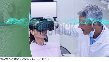 Digital waves against male doctor wearing vr headset to patient against green technology background. medical research and technology concept